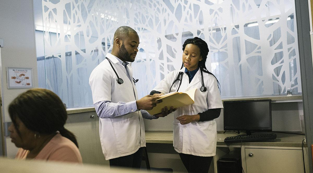 Two medical students confer in a room