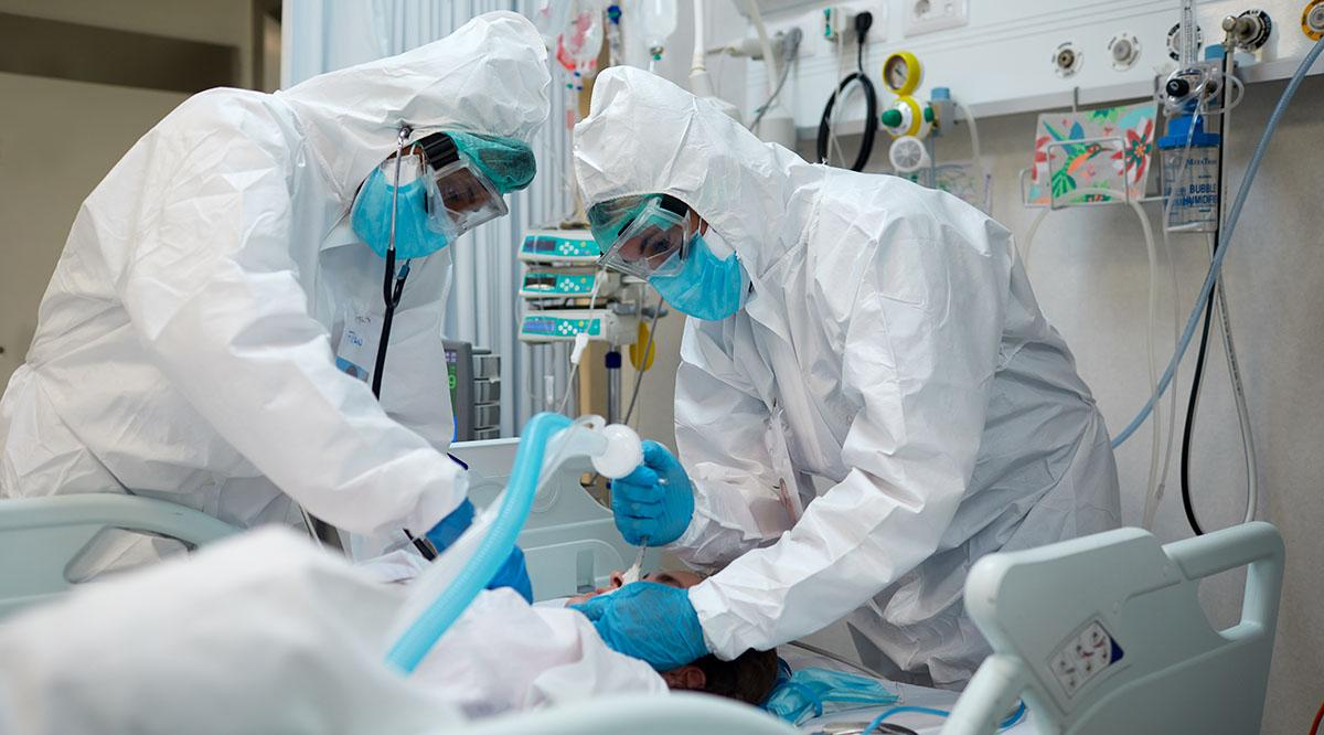 Two doctors in PPE work on a patient in the hospital