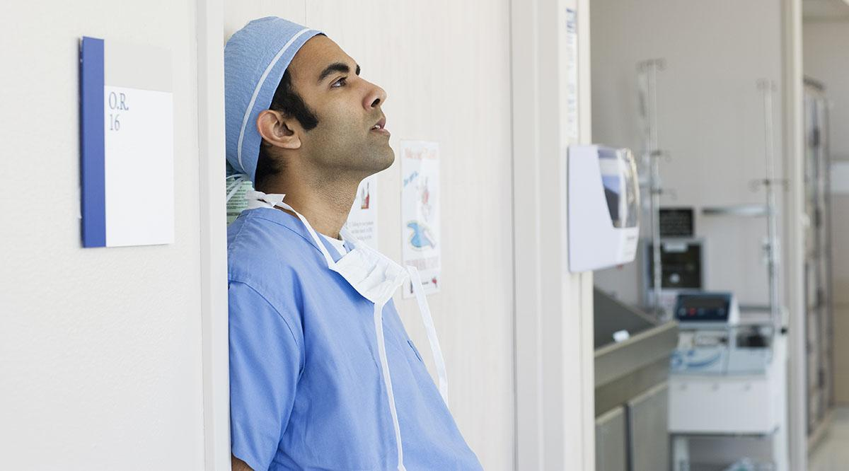 A doctor in scrubs stands against a wall looking tired