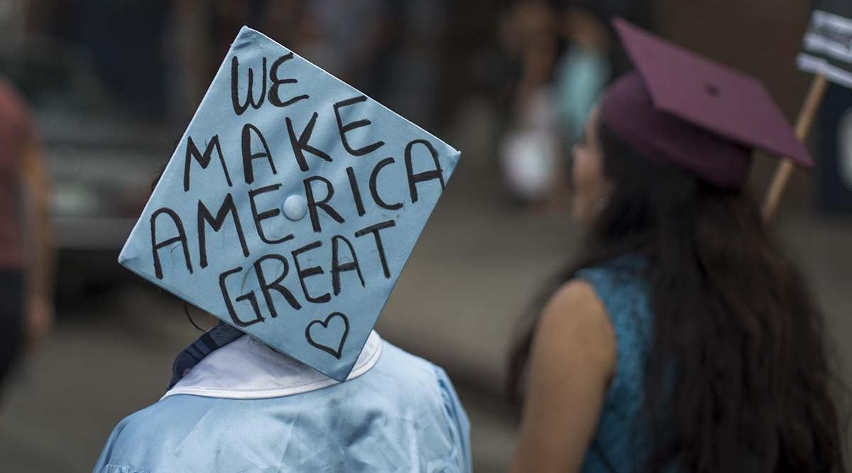 college graduate with a cap reading we make america great