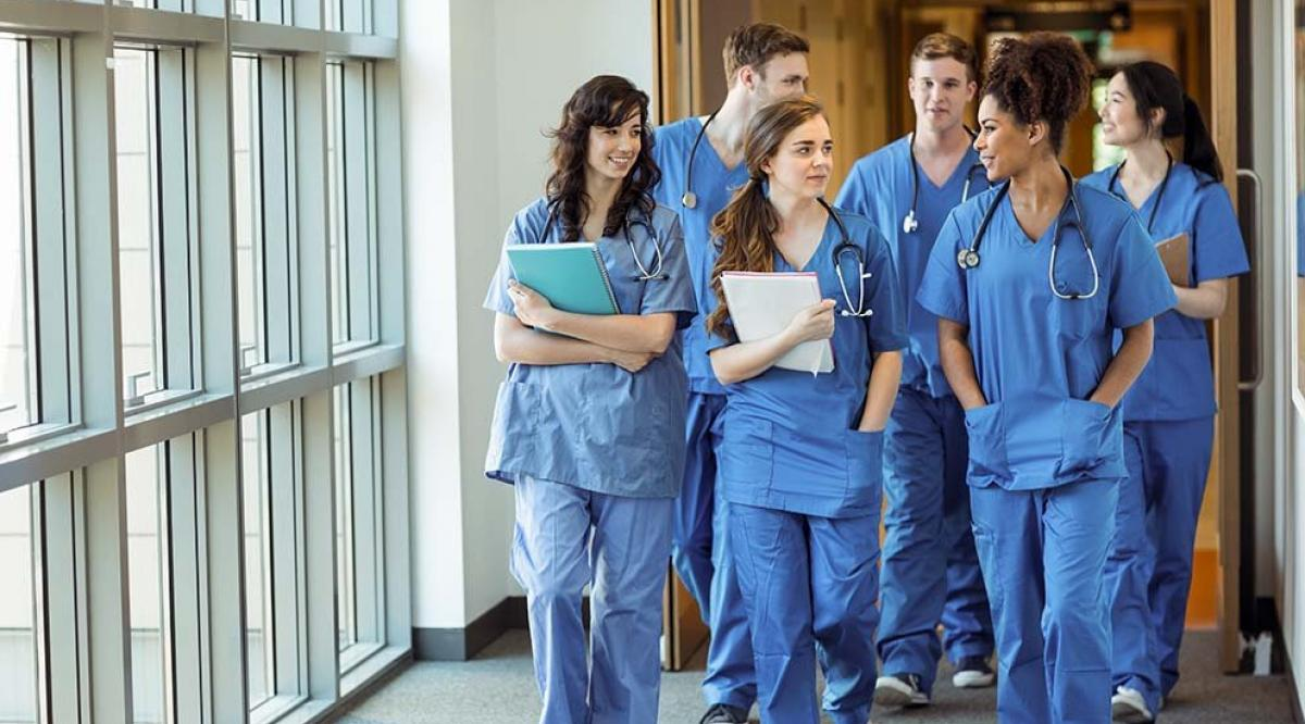 doctors in scrubs walking down a hallway