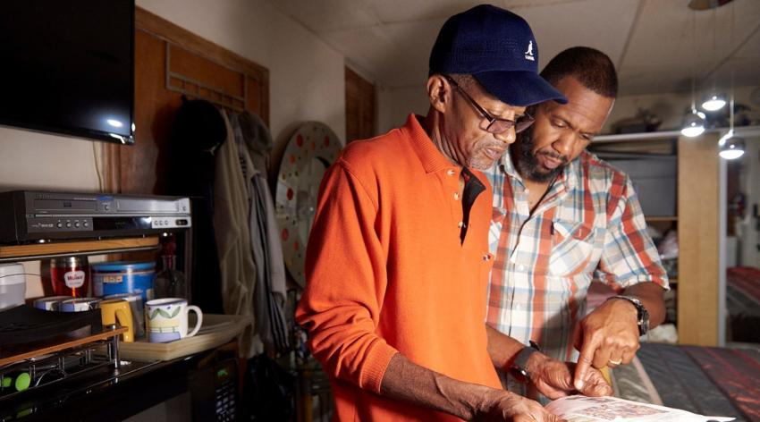 Community health worker Orson Brown (right) reviews health-related goals with a patient during a pre-pandemic home visit in Philadelphia