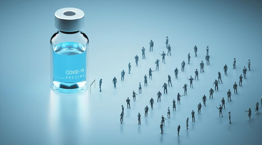 A group of people standing in a socially distant line leading to a COVID-19 vaccine bottle