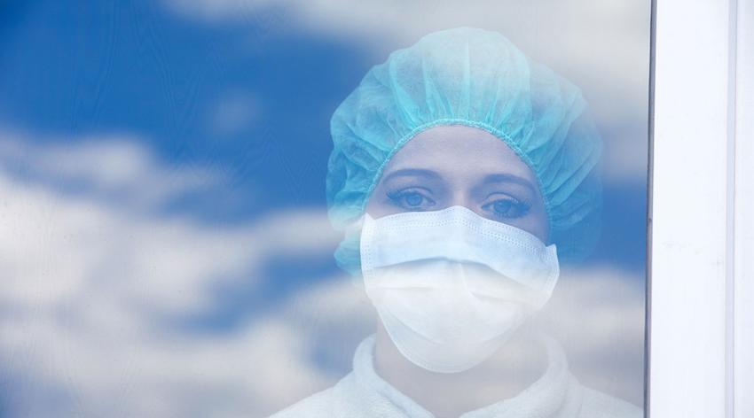 A medical worker in a mask and hairnet stares sadly out of a window