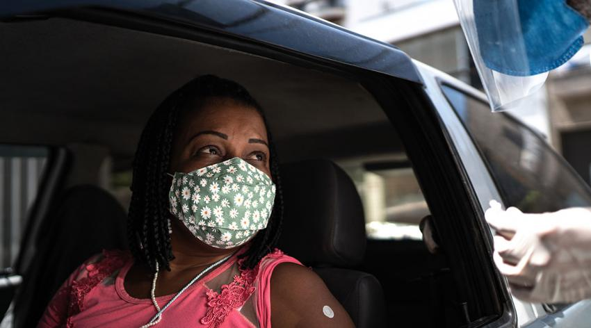 A masked woman in a car prepares to receive a vaccine from a masked worker