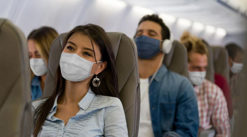 A group of masked travelers on a plane