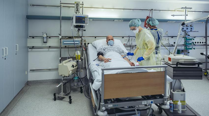 A patient in a mask is being cared for in the emergency room by two doctors in PPE