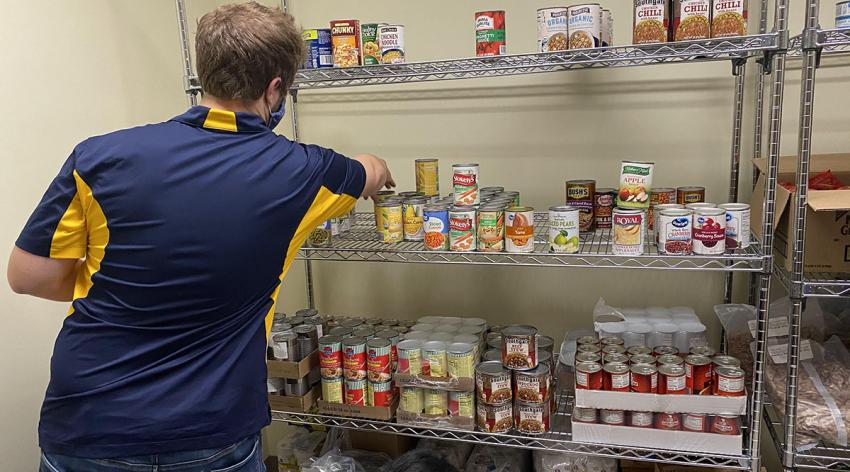 People stock the shelves of a campus food pantry at the University of Toledo in Ohio