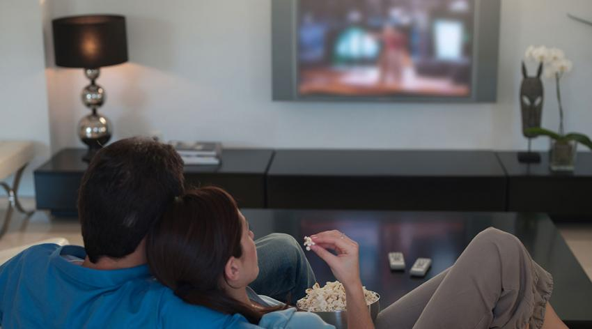 A couple watches a movie on a TV screen