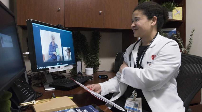 Kimberly Noel, MD, MPH, talks to a patient through a computer in her office