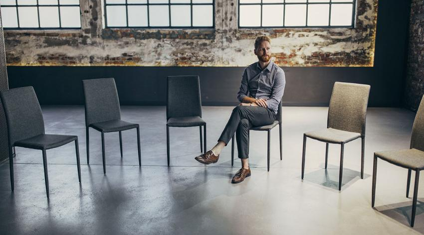A man sits alone in a circle of chairs