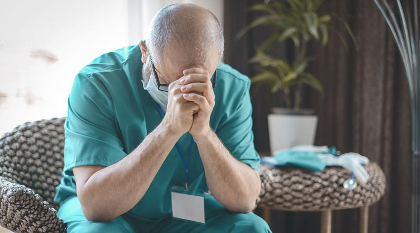 A medical provider rests his head on his hands