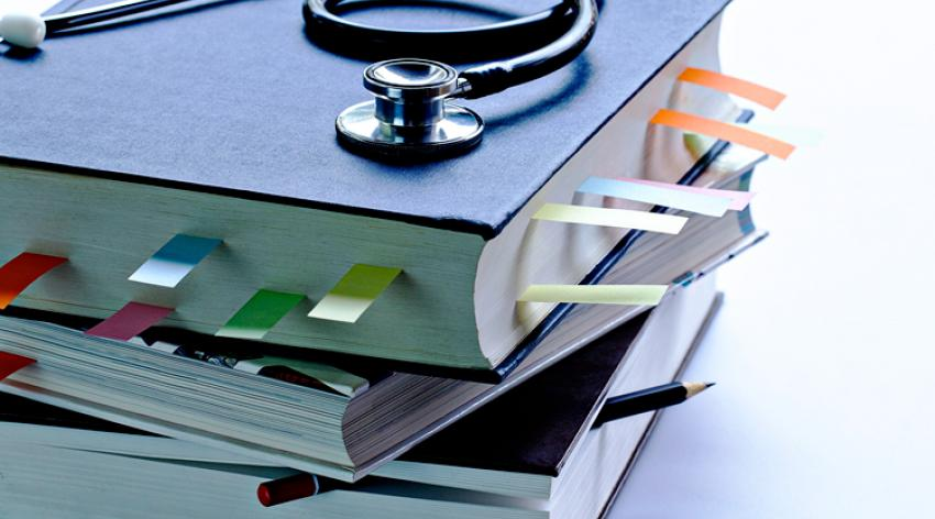 Medical student textbooks with pencil and multicolor bookmarks and stethoscope.