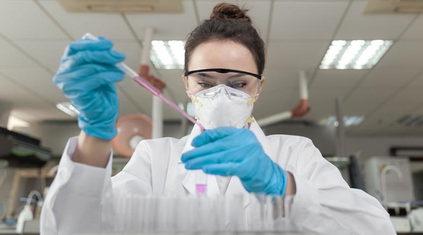 A woman runs tests using a test tube in a lab