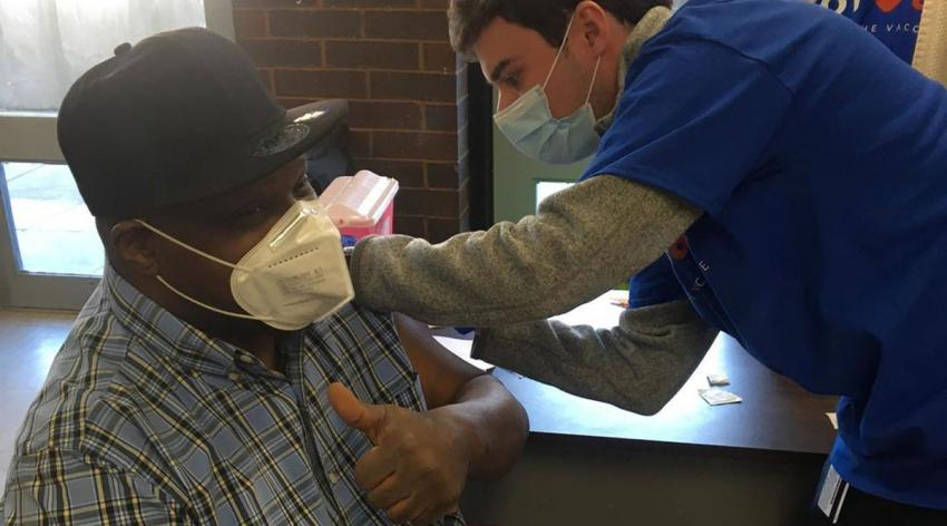 A volunteer for GOTVax, an organization focused on bringing vaccines to hard-hit communities, administers a vaccine to a resident of a Boston Housing Authority building in an under-resourced neighborhood.