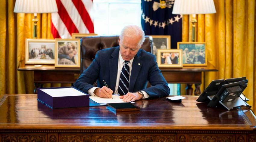 Biden at desk signing bill
