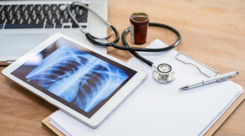 A laptop, a tablet showing a lung x-ray scan, a stethoscope, a notepad, and a pen on a table