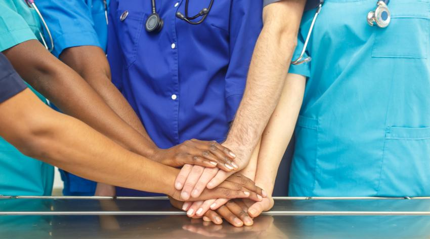 Diverse group of doctors stacking hands in an operating room table.