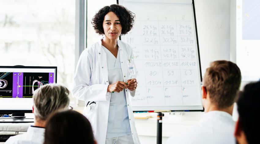 A female medical faculty standing in front of her students inside a classroom. Behind