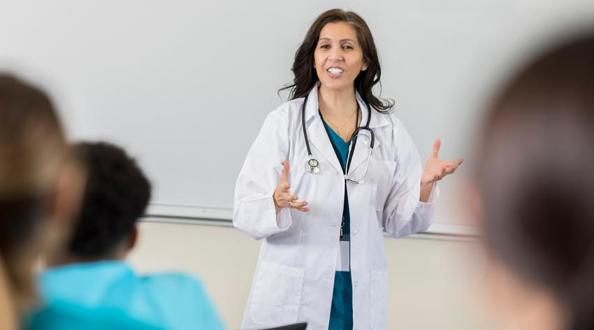 A doctor stands at the front of a classroom giving a lecture to medical students