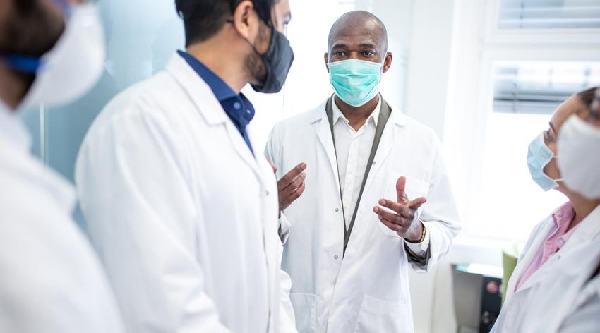 A small group of doctors wearing masks having a conversation in a hospital