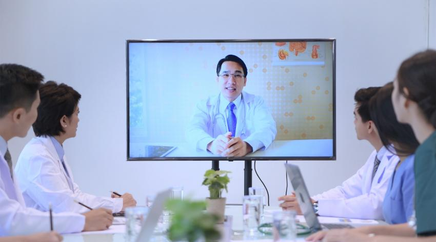 A male doctor teaches a group of fellow health professionals over the computer.
