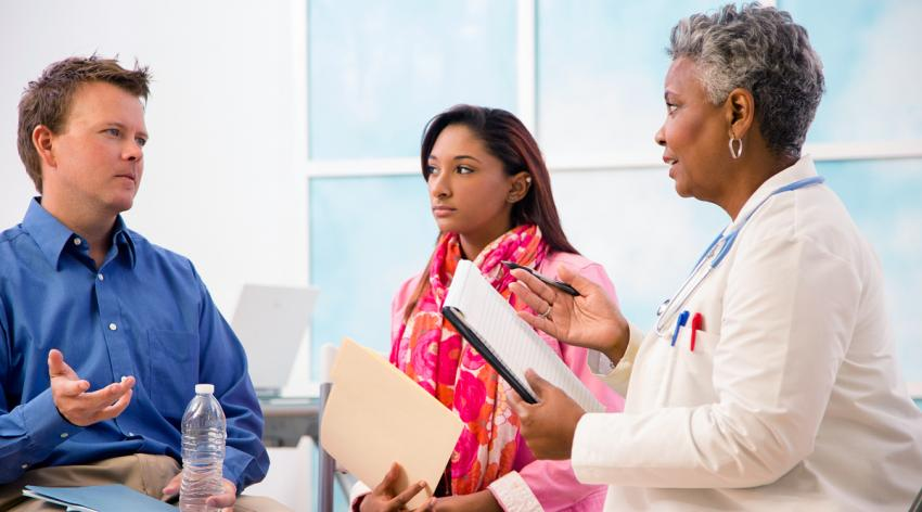 A female doctor talking with man and woman patients in an office or clinic.