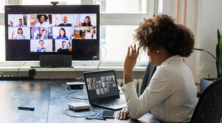 Rear view of a businesswoman having a meeting with team over a video conference in office board room.
