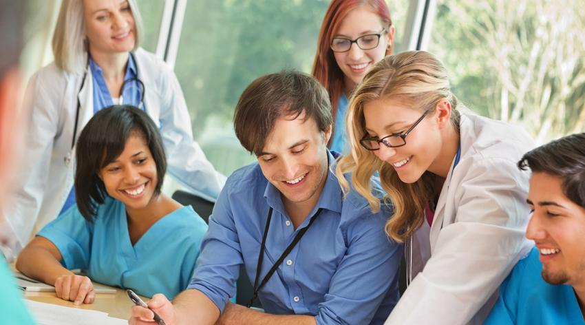Medical residents sitting around a table reviewing a document.